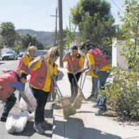 Church members clean-up in front of residence.