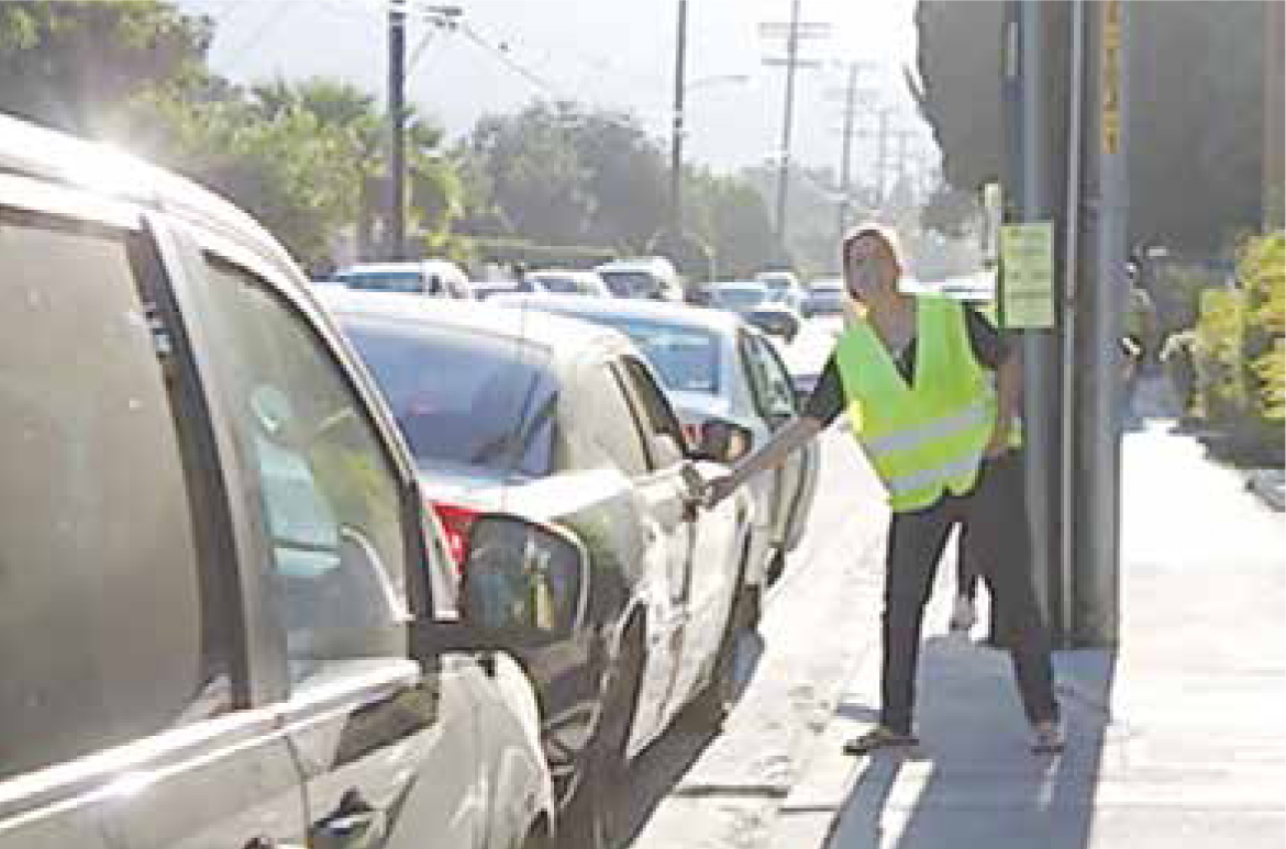 A volunteer crossing guard helps out.