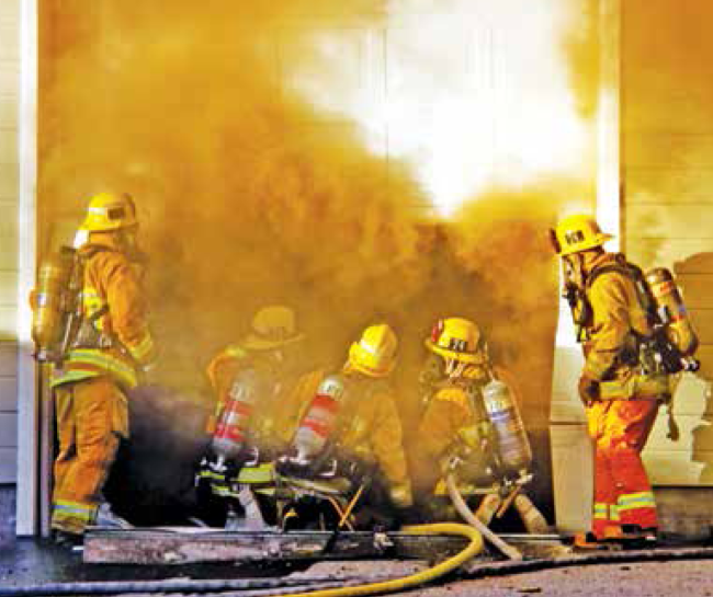 Firefighters wait for garage smoke to vent so they can see where the fire is.