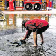 A homeless person washes his clothes in rainwater at Sunland Park.