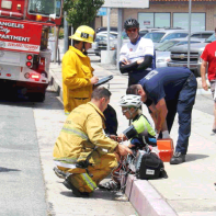 Firefighters tend to two bicyclists who were struck by a car in the bicycle lane last Thursday next to Starbucks.