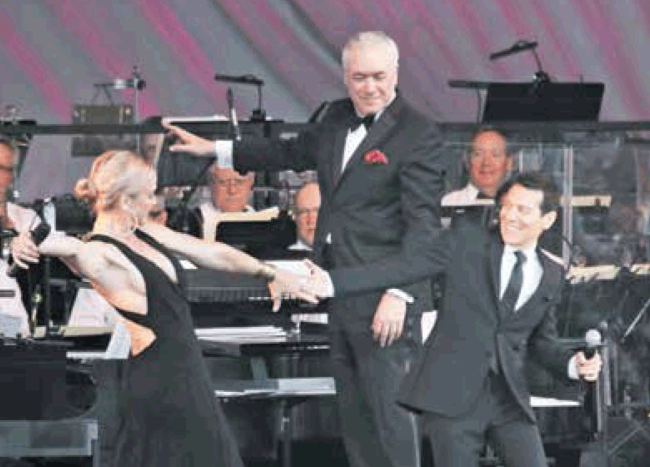 Storm Large and Michael Feinstein swing to the music conducted by Larry Blank.