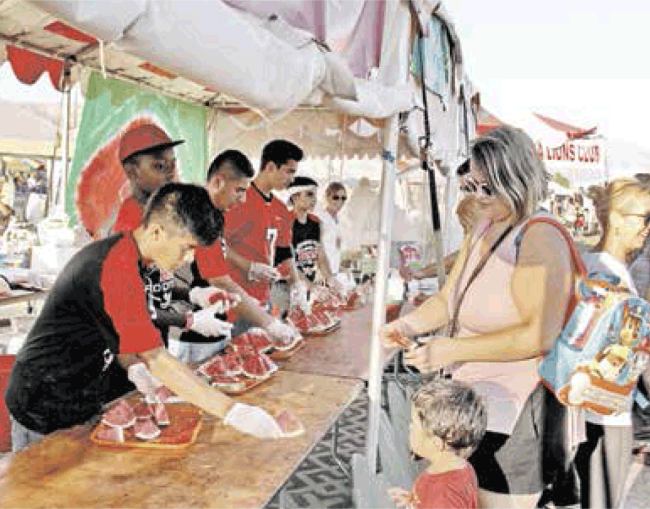 Verdugo Dons dish out cold watermelon to the revelers!