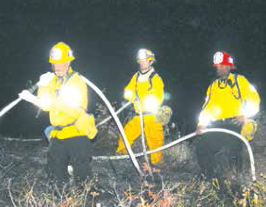 Fire fighters hose down the third fire in two days on the La Tuna Canyon on-ramp